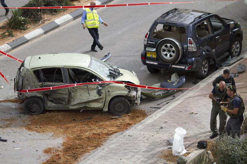 Israeli police engineers look at a camera as they examine the site after a rocket fired by Palestinian militants from the Gaza Strip hit the city of Ashdod, southern Israel, Monday, March 12, 2012. Israeli airstrikes killed three Palestinian civilians and two militants in the Gaza Strip on Monday and Palestinian rocket squads barraged southern Israel in escalating fighting that defied international truce efforts. A high school student, a father and daughter were among the dead. The cross-border violence, touched off by Israel's killing of a top Palestinian militant leader on Friday, has been the worst exchange of fire between Israel and the Hamas-ruled territory in months.(AP Photo/Ariel Schalit)