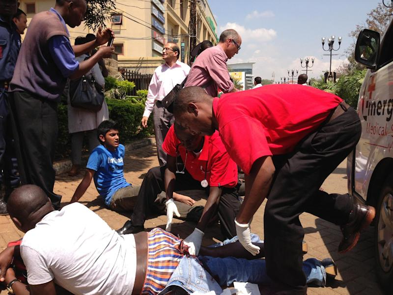 An injured man is trreated outside an upscale shopping mall, seen background, in Nairobi, Kenya Saturday Sept. 21 2013, where shooting erupted when armed men attempted to rob a shop, according to police. Witnesses say a half dozen grenades also went off along with lobbies of gunfire that started at midday. (AP Photo/ Jason Straziuso)