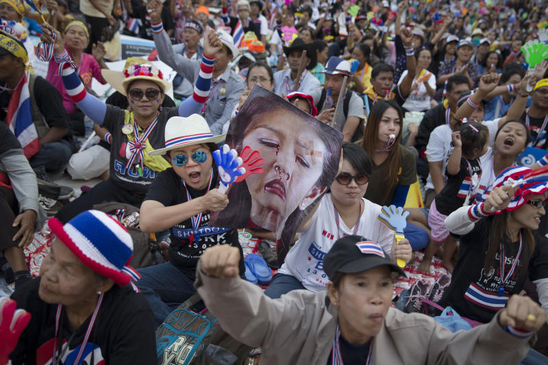 An anti-government People's Democratic Reform Committee (PDRC) protester beats an effigy of Prime Minister Yingluck Shinawatra as the surrounding crowd cheers at an encampment in the Pathumwan district, Thursday, Jan. 16, 2014, in Bangkok. Throngs of whistle-blowing protesters were on the march again in the Thai capital Thursday, surrounding several government offices they had not previously interfered with to keep up pressure on Yingluck to resign and call off next month's election. (AP Photo/John Minchillo)