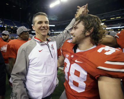 Ohio State head coach Urban Meyer, left, celebrates with one of his players after winning the Big Ten title game. (AP)
