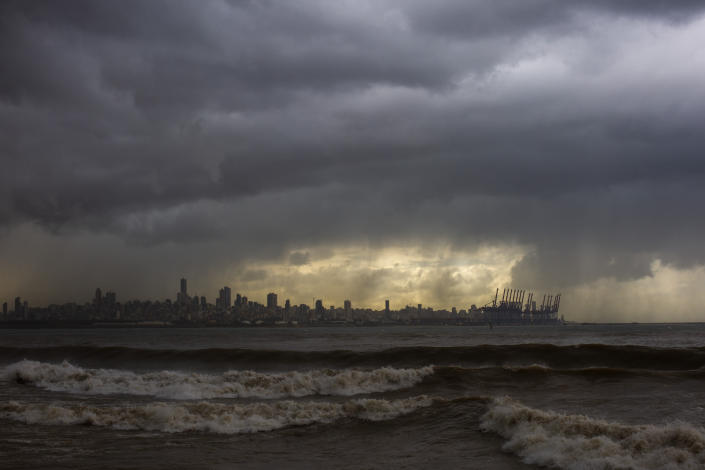 Heavy clouds hover over Beirut as waves crash on the seawall of the corniche, in Dbayeh, Lebanon, Wednesday, Feb. 17, 2021. Storm Joyce hit late Tuesday with gale force winds registering up to 100 km/h (62 miles/h). (AP Photo/Hassan Ammar)