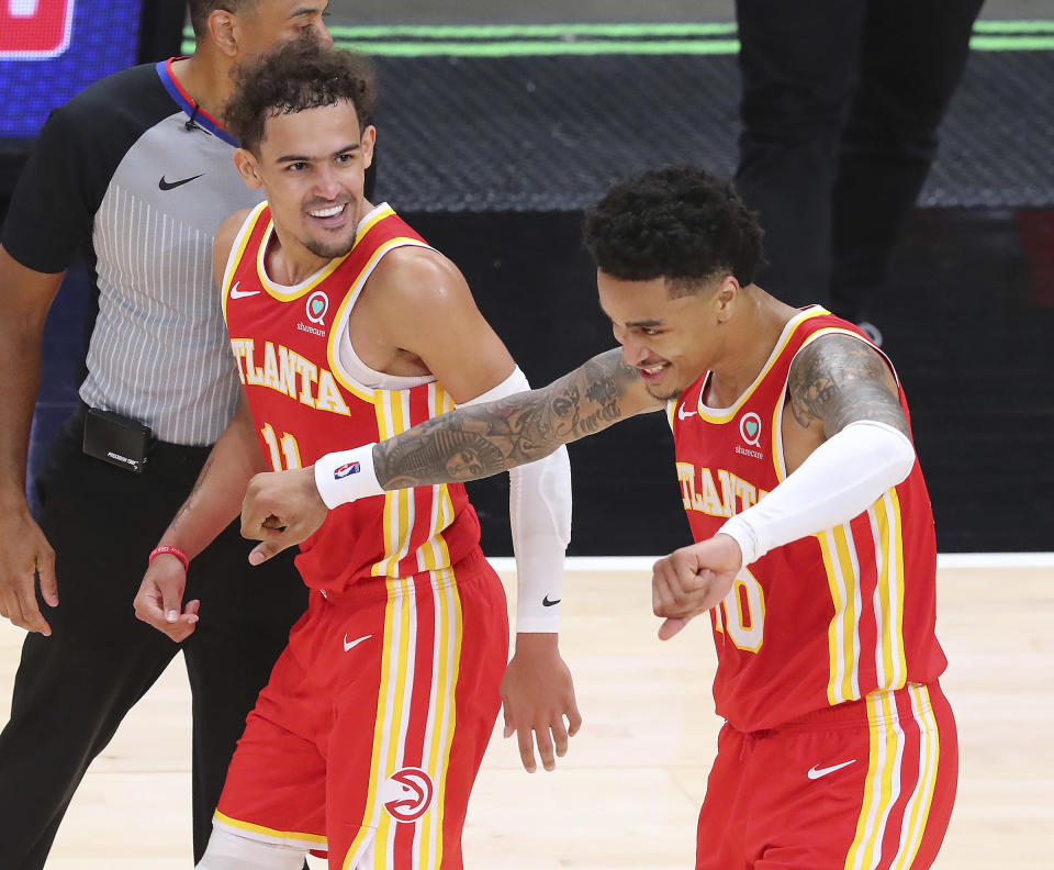 Atlanta Hawks Trae Young, left, celebrates with John Collins after Collins hit a three pointer in the final minute of an NBA basketball game against the Washington Wizards Wednesday, May 12, 2021, in Atlanta. (Curtis Compton/Atlanta Journal-Constitution via AP)