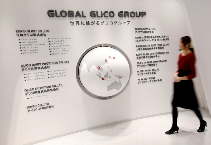 Employee of Ezaki Glico walks past a map displaying the companies in the Global Glico Group at Glicopia East, a museum of the company located next to its Kitamoto factory