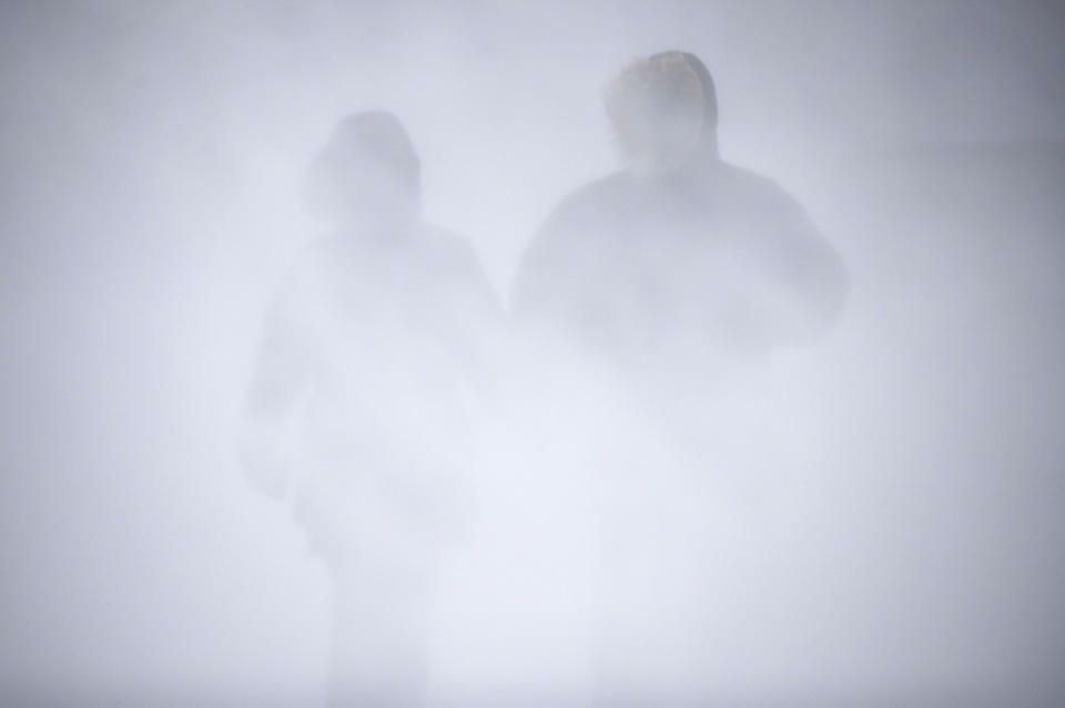 Angel Fuchs, left, and Marc Veillet enjoy a walk in Canal Park as the snow and wind picked up, Wednesday, Dec. 23, 2020 in Duluth, Minn. (Alex Kormann/Star Tribune via AP)