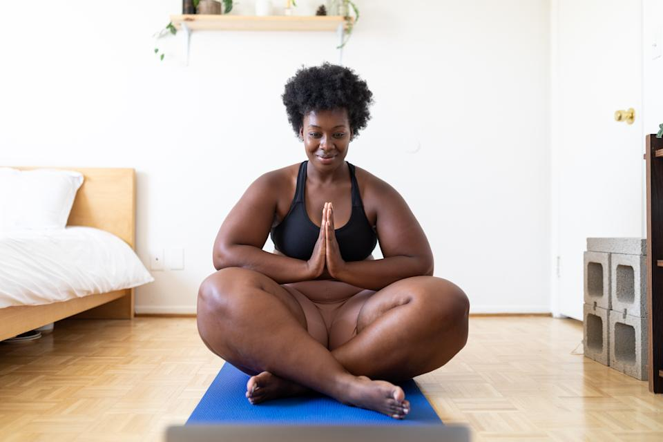 Healthy african woman doing yoga workout at home in front of her laptop. Female in sportswear watching video tutorial online on her laptop and doing yoga meditation. Exercising at home during corona virus lockdown.