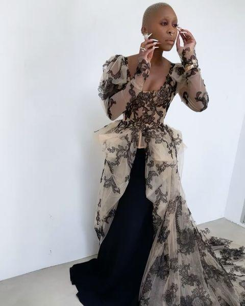 <p>in a custom Vera Wang Collection split-away gown featuring hand draped sleeves, black hand-cut lace, worn over a black silk floor-length flared skirt, plus Tiffany & Co. jewelry.</p>