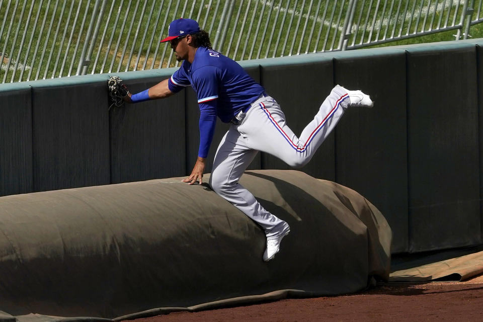 Texas Rangers' Ronald Guzmán collides with the tarp trying to catch a foul ball hit by Los Angeles Angels' Luis Rengifo during the third inning of a spring training baseball game, Wednesday, March 3, 2021, in Tempe Ariz. (AP Photo/Matt York)