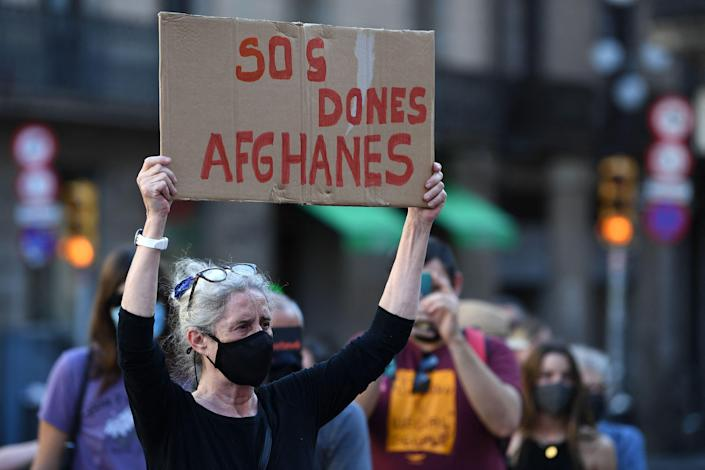 """A woman holds up a sign reading """"SOS Afghan women"""" as she attends a demonstration called by """"Ca la Dona"""" feminist association in support of Afghan women and girls, in Barcelona on Wednesday."""