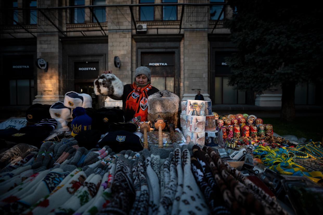 A Kiev street vendor arranges her stall with various items, among them toilet paper with Russian President Putin's portrait. (Photo: Agron Dragaj for Yahoo News)