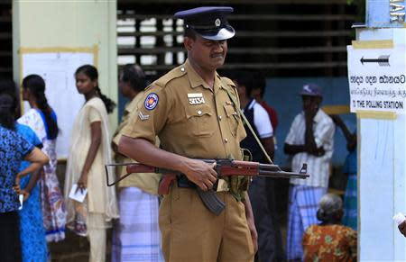 A police officer stands guard next to Tamil voters at a polling station during the first provincial polls in 25 years in Jaffna