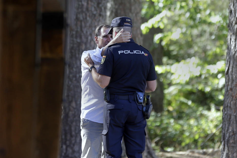 Adrian Federighi, brother in-law of former ski racer Blanca Fernandez Ochoa and spokesperson for the family, embraces a police officer after the search near Cercedilla, just outside of Madrid, Spain, Wednesday Sept. 4, 2019. Spanish police have found the body of former ski racer and Olympic medalist Blanca Fernandez Ochoa in a mountainous area near Madrid. Police said a tracking dog came across a woman's body near a peak in the forested area on Wednesday after days of searching for Spain's first female medalist in the Winter Olympics.(AP Photo/Paul White)