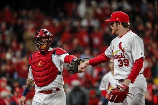 St. Louis Cardinals starting pitcher Miles Mikolas is congratulated by catcher Yadier Molina after the first inning of Game 1 of the National League Championship Series baseball game against the Washington Nationals Friday, Oct. 11, 2019, in St. Louis. (AP Photo/Jeff Roberson)