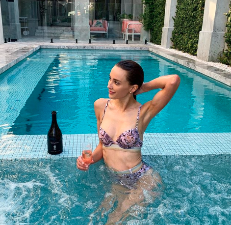 Bec Judd poses in luxury pool in purple bikini with bottle of champagne
