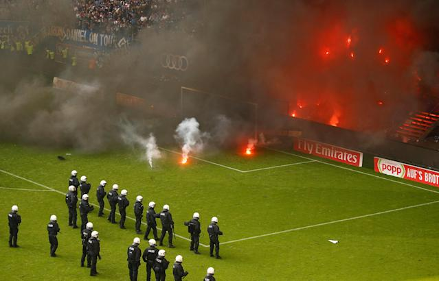 Soccer Football - Bundesliga - Hamburger SV v Borussia Moenchengladbach - Volksparkstadion, Hamburg, Germany - May 12, 2018 Riot police stand back as the Hamburg fans let off flares and throw them on to the pitch REUTERS/Morris Mac Matzen DFL RULES TO LIMIT THE ONLINE USAGE DURING MATCH TIME TO 15 PICTURES PER GAME. IMAGE SEQUENCES TO SIMULATE VIDEO IS NOT ALLOWED AT ANY TIME. FOR FURTHER QUERIES PLEASE CONTACT DFL DIRECTLY AT + 49 69 650050