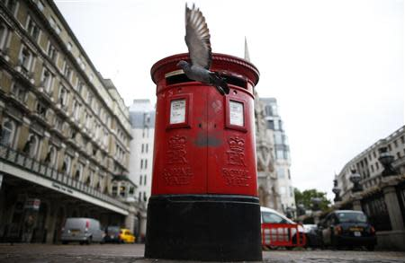A pigeon flies past a Royal Mail post box outside Charing Cross station in central London, October 8, 2013. REUTERS/Andrew Winning