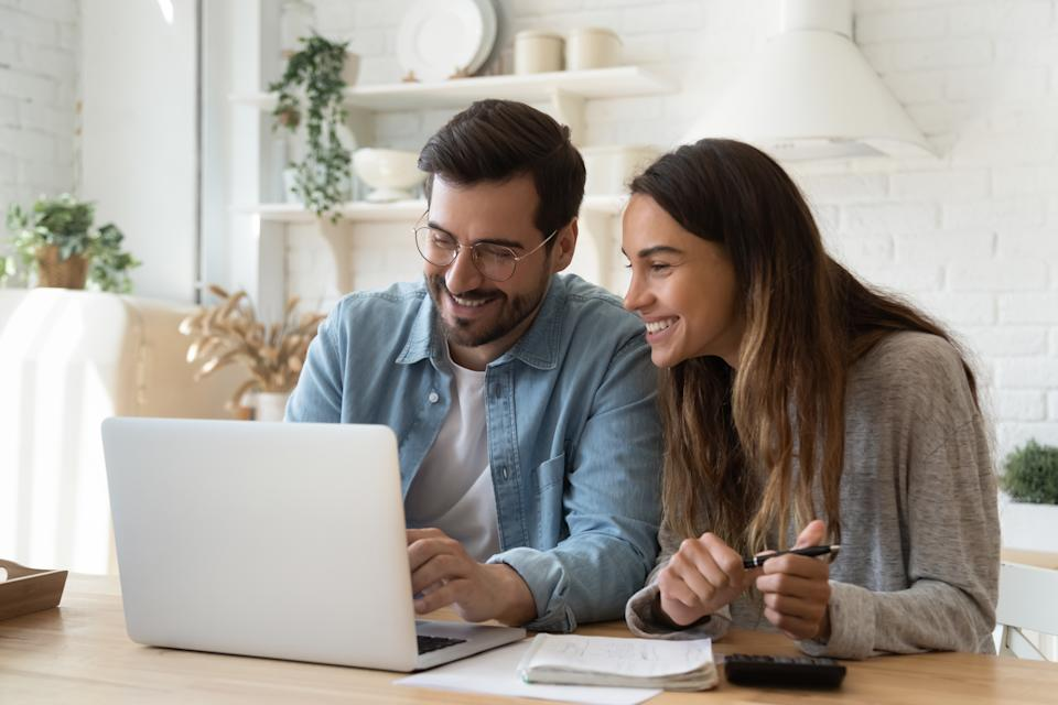 Happy young couple husband and wife using laptop computer looking at screen pay bills online in app calculate mortgage investment payment on website planning budget discuss finances sit at home table