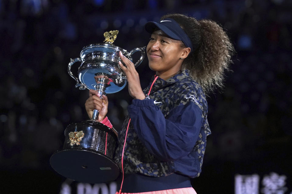 FILE - Japan's Naomi Osaka holds the Daphne Akhurst Memorial Cup after defeating United States Jennifer Brady in the women's singles final at the Australian Open tennis championship in Melbourne, Australia, in this Saturday, Feb. 20, 2021, file photo. Naomi Osaka was going to be at the center of attention during the Tokyo Olympics no matter what. She is a tennis superstar who owns four Grand Slam titles and is the highest-earning female athlete in the world.(AP Photo/Mark Dadswell, FIle)