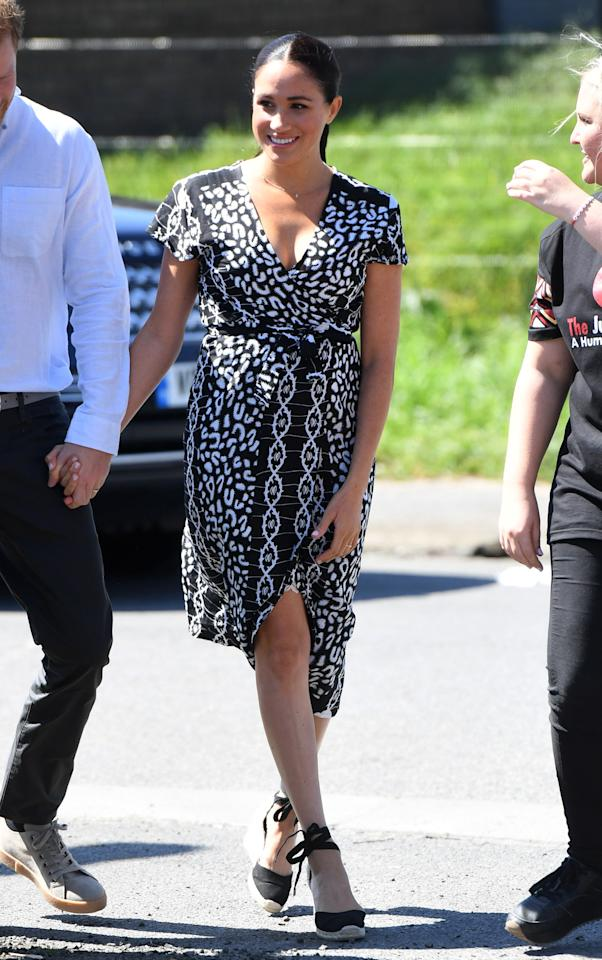 Markle kicked off the tour in a patterned wrap dress from Mayamiko, a sustainable fashion brand that sources textiles from Malawi, and her Castañer espradrille wedges.