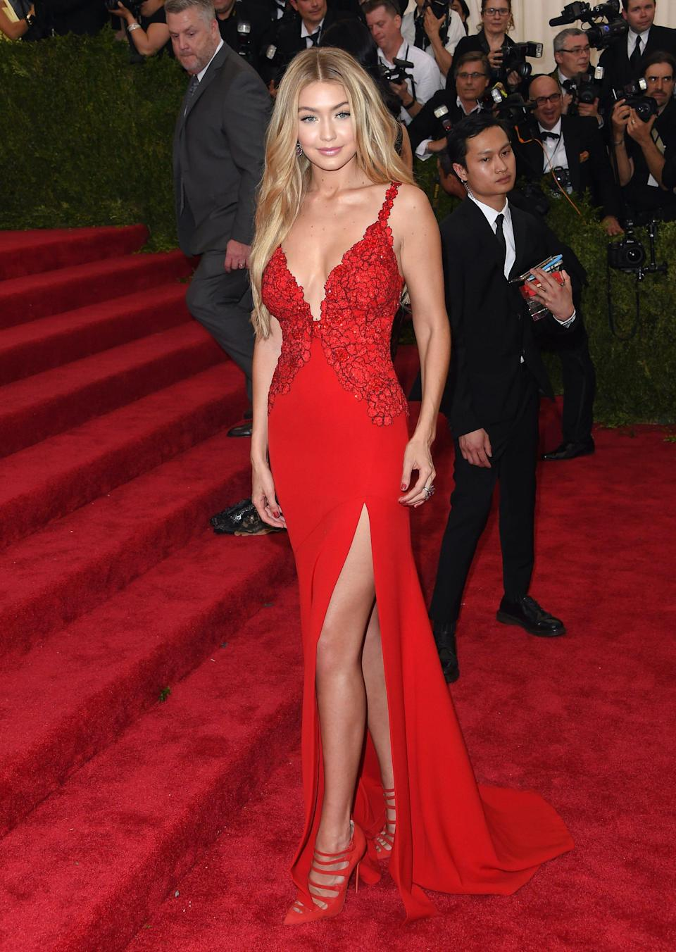 Gigi Hadid wears a red dress with a slit on a red carpet.
