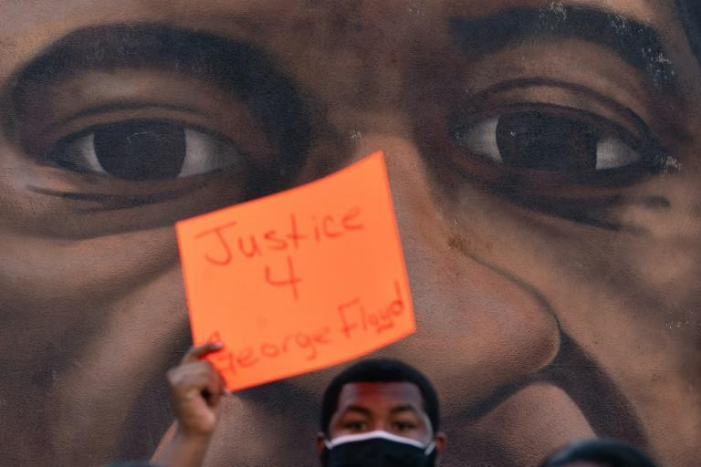 A man holds up a sign in front of a mural of George Floyd following the guilty verdict the trial of Derek Chauvin on April 20, 2021, in Atlanta, Georgia