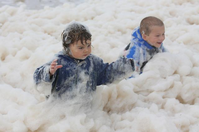 Children play with ocean foam in Burleigh Heads as Queensland experiences severe rains and flooding from Tropical Cyclone Oswald on January 28, 2013 in Gold Coast, Australia. Hundreds have been evacuated from the towns of Gladstone and Bunderberg while the rest of Queensland braces for more flooding. (Photo by Chris Hyde/Getty Images)