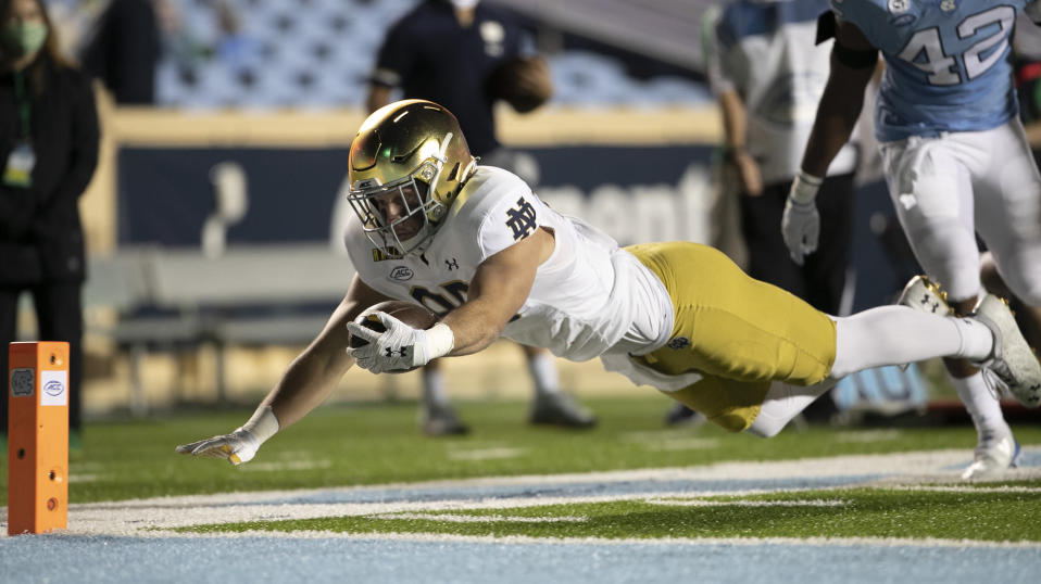 Notre Dame's George Takacs (85) gets past North Carolina's Tyrone Hopper (42) picking up 13 yards on a pass completion from quarterback Ian Book (12) and dive toward the goal line, but is stopped short during the fourth quarter of an NCAA college football game Friday, Nov. 27, 2020, in Chapel Hill, N.C. (Robert Willett/The News & Observer via AP, Pool)