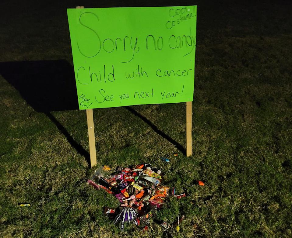 A sign outside a home tells people 'no candy' because a child with cancer is inside. Lollies sit at the base of the sign.