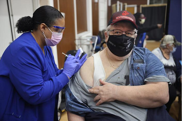 man in a mask getting his third booster shot of Pfizer vaccine injected into his right arm by a healthcare worker (also masked).