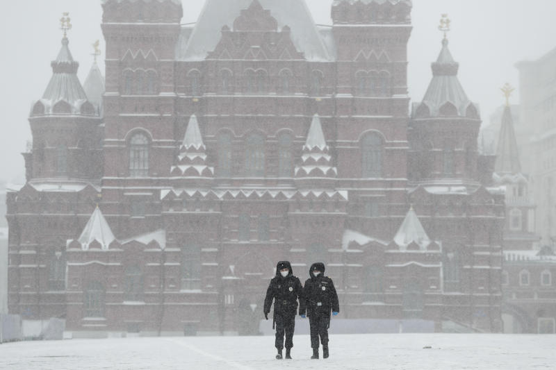 Police officers walk across an empty Red Square in Moscow, Russia, Tuesday, March 31, 2020. The Russian capital has woken up to a lockdown obliging most people in the city of 13 million to stay home. The government ordered other regions of the vast country to quickly prepare for the same as Moscow, to stem the spread of the new coronavirus. The new coronavirus causes mild or moderate symptoms for most people, but for some, especially older adults and people with existing health problems, it can cause more severe illness or death. (AP Photo/Pavel Golovkin)