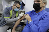 Pharmacist Ali Lahib, left, administers a flu shot to Bernard Mathonet in a drugstore Wednesday, Oct.14, 2020 in Paris. France launched a flu vaccine campaign Tuesday in an effort to avoid facing another epidemic peak as the coronavirus is spreading rapidly in the country. French health authorities have issued official recommendations to prevent potential shortages of flu vaccine, which they fear might happen amid increased demand because of the COVID-19 pandemic. (AP Photo/Lewis Joly)