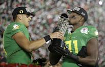 Oregon quarterback Marcus Mariota, left, and linebacker Tony Washington celebrate with the trophy after a 59-20 win over Florida State during the second half of the Rose Bowl NCAA college football playoff semifinal, Thursday, Jan. 1, 2015, in Pasadena, Calif. (AP Photo/Jae C. Hong)