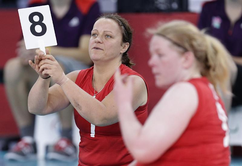 Martine Wright, left, of Britain holds up the No 8 sign as she come on as a substitute to play against Ukraine, during their women' sitting volleyball match at the 2012 Paralympics games, Friday, Aug. 31, 2012, in London. On July 7, 2005, four suicide bombers detonated explosives on London's transit system, killing 52 commuters and the four attackers. Wright was among the injured on 7/7, losing both her legs. Seven years later, she's been transformed into an athlete, a Paralympian.(AP Photo/Alastair Grant)