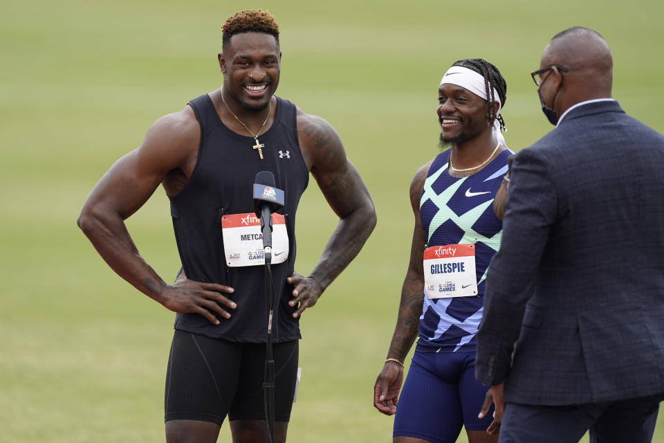 Seattle Seahawks wide receiver DK Metcalf, left, is interviewed with Cravon Gillespie after they competed in the second heat of the men's 100-meter dash prelim during the USATF Golden Games at Mt. San Antonio College Sunday, May 9, 2021, in Walnut, Calif. Gillespie won the heat. (AP Photo/Ashley Landis)