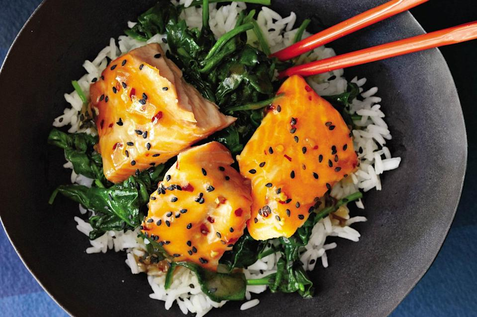 """Skinless salmon fillets are cooked with a luscious glaze of garlic, lime, maple syrup, and soy in this heart-healthy grain bowl. Black sesame seeds make a pretty garnish. <a href=""""https://www.epicurious.com/recipes/food/views/asian-salmon-bowl-with-lime-drizzle-51101210?mbid=synd_yahoo_rss"""" rel=""""nofollow noopener"""" target=""""_blank"""" data-ylk=""""slk:See recipe."""" class=""""link rapid-noclick-resp"""">See recipe.</a>"""