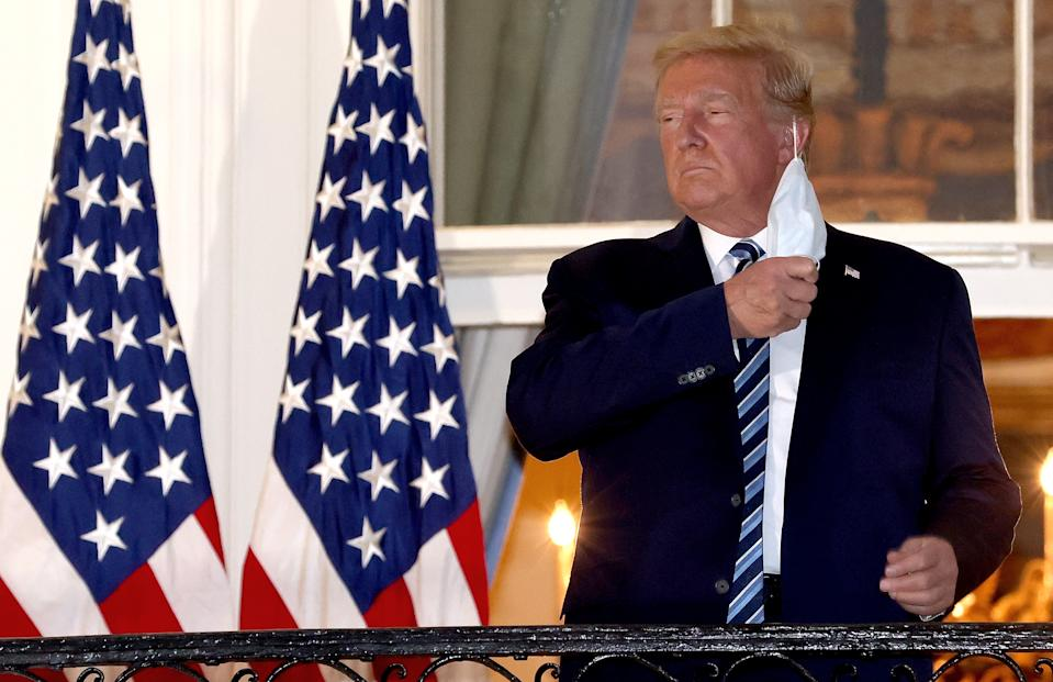 US President Donald Trump removes his mask upon return to the White House afgter battling Covid-19. Source: Getty