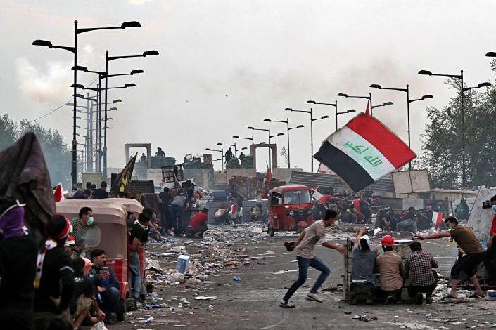 Anti-government protesters take cover while Iraqi Security forces fire tear gas and close the bridge leading to the Green Zone, during a demonstration in Baghdad, Iraq, Sunday, Oct. 27, 2019. Protests have resumed in Iraq after a wave of anti-government protests earlier this month were violently put down. (Photo: Khalid Mohammed/AP)