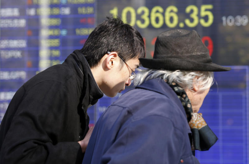 People walk by an electronic stock board of a securities firm in Tokyo, Thursday, Dec. 27, 2012. Asian markets have risen amid optimism that Japan's new leaders will stimulate its sluggish economy. (AP Photo/Koji Sasahara)