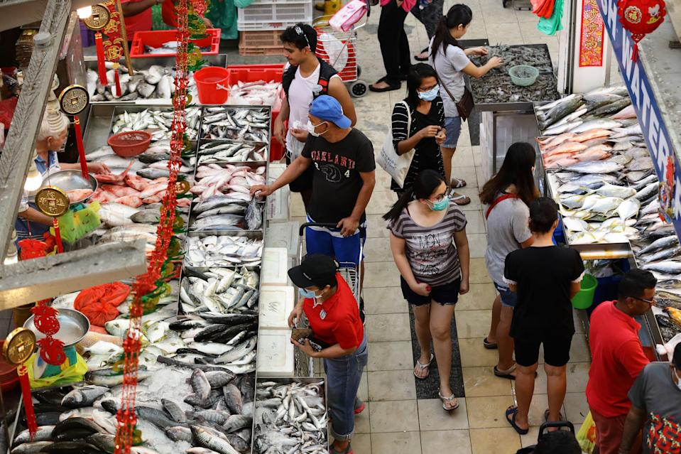 People seen shopping for seafood at a wet market on 28 March 2020. (PHOTO: Getty Images)