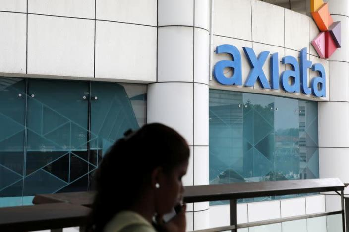 A woman walks past the Axiata headquarters building in Kuala Lumpur
