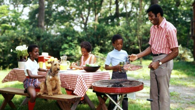 Family at picnic table beside a grill where they prepare to grill steaks