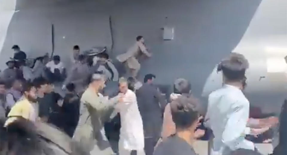 People try to cling to military planes in a desperate move to leave the country. Source: Twitter