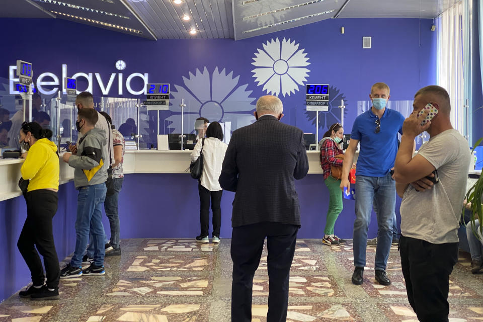 People return their tickets to fly abroad at an office of Belavia, the Belarusian national carrier, in Minsk, Belarus, Friday, May 28, 2021. The European Union has banned flights from Belarus after a Ryanair jetliner was diverted to Minsk on Sunday, May 23, 2021, and authorities arrested a dissident journalist who was aboard. Those who want to leave Belarus are finding few options. (AP Photo)