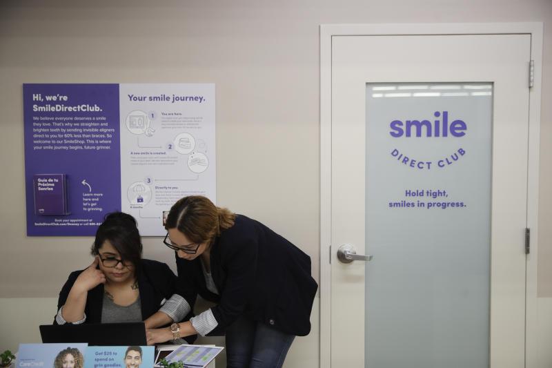 Dental assistants Itzel Barrueta, left, and Jessica Buendia go over appointments at SmileDirectClub's SmileShop located inside a CVS store Wednesday, April 24, 2019, in Downey, Calif. CVS Health is venturing into dental care with plans to offer the relatively new teeth-straightening service. (AP Photo/Jae C. Hong)