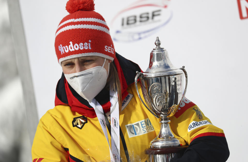 Winner, Germany's Tina Hermann holds the trophy on the podium during the women's skeleton race at the Bobsleigh and Skeleton World Championships in Altenberg, Germany, Friday, Feb.12, 2021. (AP Photo/Matthias Schrader)