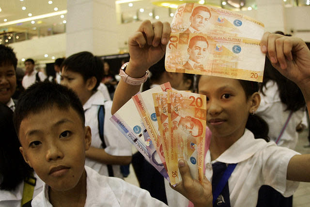 Filipino pupils proudly display their newly changed Philippine Peso bills during the launch of an advocacy against the production and proliferation of fakes and counterfeits held in a suburban mall in Quezon City, northeast of Manila.