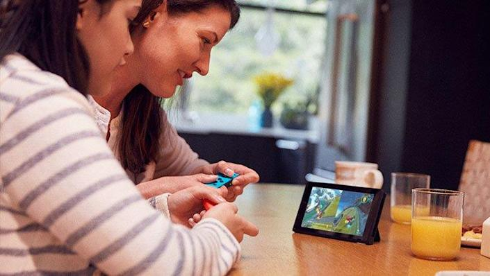 Mother and daughter enjoy a fun Nintendo Switch game together.