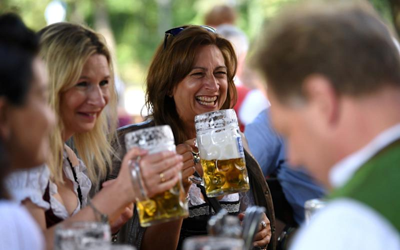 People attend the tapping of the first barrel at a beer garden in Munich - REUTERS/Andreas Gebert