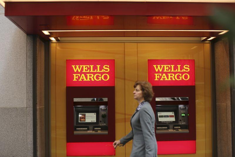 File photo of a woman walking past teller machines at a Wells Fargo bank in San Francisco
