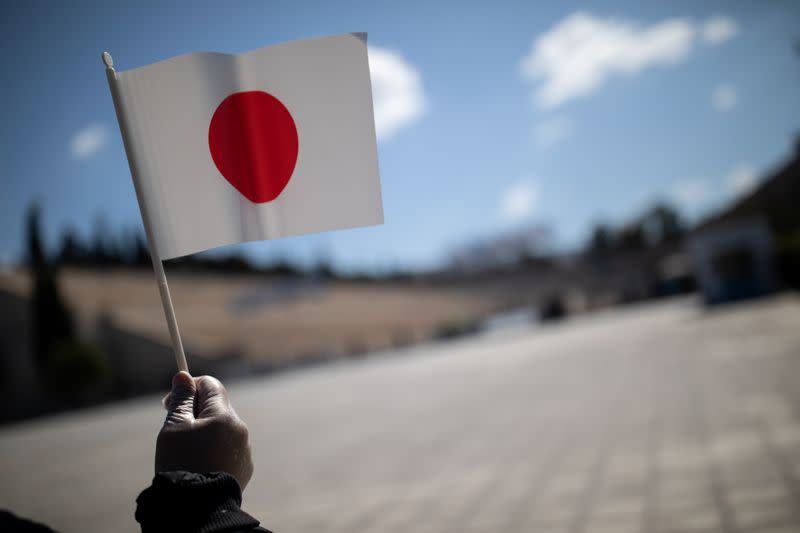 A man wearing protective plastic gloves waves a Japanese flag outside the Panathenaic Stadium in Athens