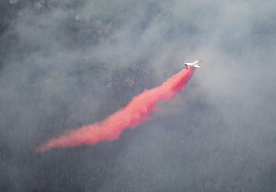 An aircraft drops red fire retardant onto the Greenwood Fire, about 50 miles north of Duluth, Minn., Tuesday, Aug. 17, 2021, as seen from an airplane above the temporary flight restriction zone. (Alex Korman/Star Tribune via AP)